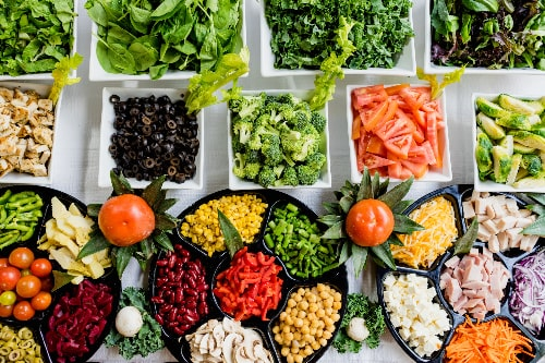 Refrigerator salad bar containing vegetables, beans, and protein for a healthy meal prep idea.
