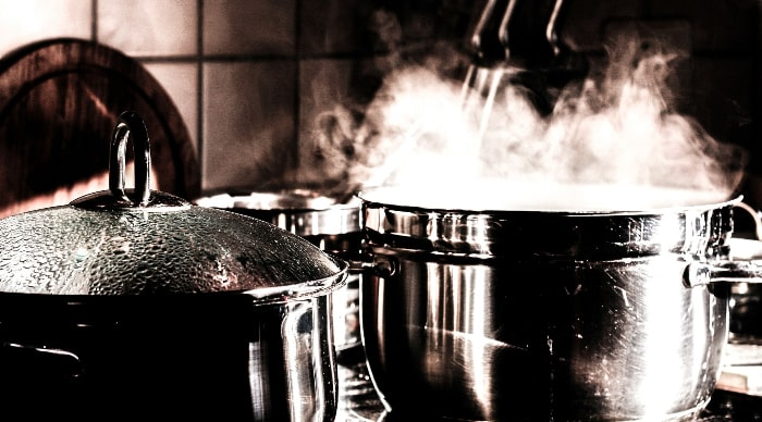 Silver cooking pots on a stove. Healthy meals are cooked at home with high-quality ingredients.